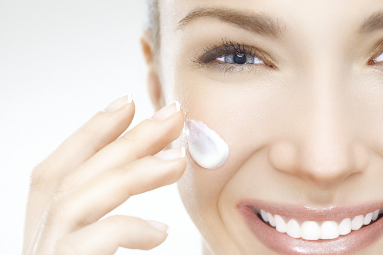 Close-up of a beautiful woman applying cream on her face